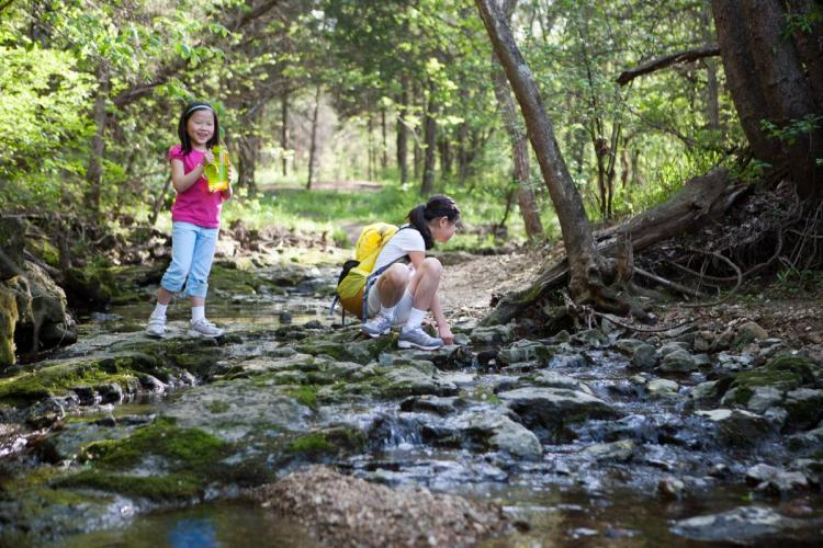 Two children exploring a stream at Runge CNC