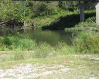 View across a gravel area towards the access ramp for the stream