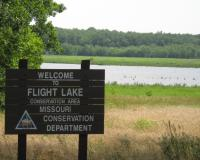 Welcome sign with lake in the background.