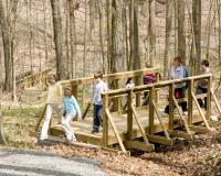 children walking over a wooden bridge on a trail