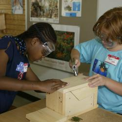 Two girls build a birdhouse at the Discovery Center in Kansas City.